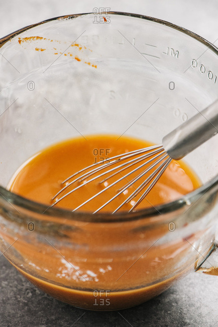 Measuring bowl with marinade and a wire whisk