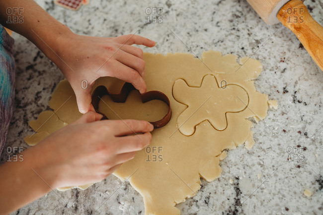 Overview of girl hands cutting out a cookie with cookie cutter