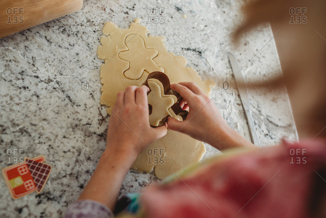 Overhead view of girl cutting out cookies with cookie cutter