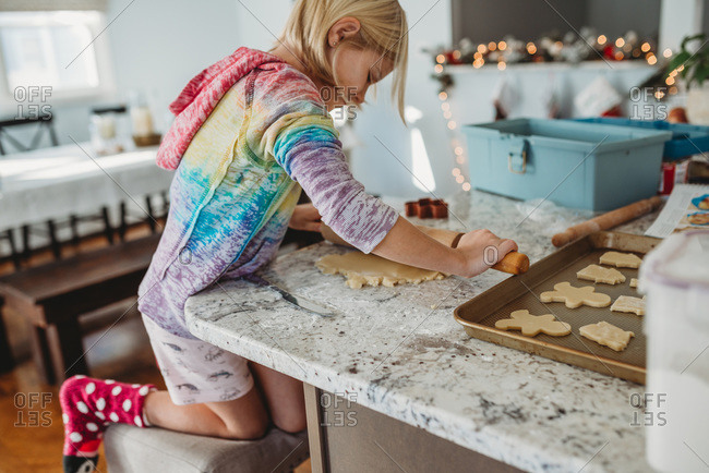 Young Girl using rolling pin to roll out dough