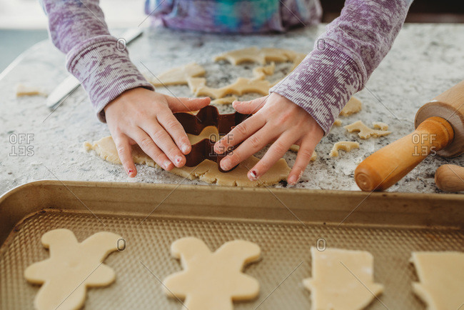 Young Girl hands using cookie cutter on cookie dough
