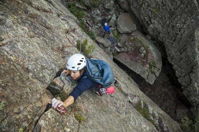 Woman rock climbs Matron North Face, Flatirons near Boulder, Colorado