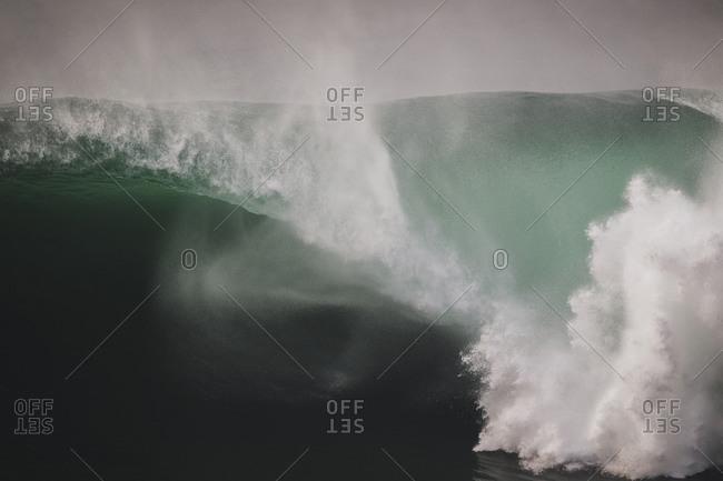 Massive wave spiting a huge barrel under the cliffs of Moher, Ireland