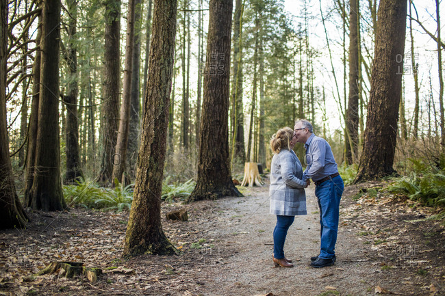 Retired couple kissing in the woods.