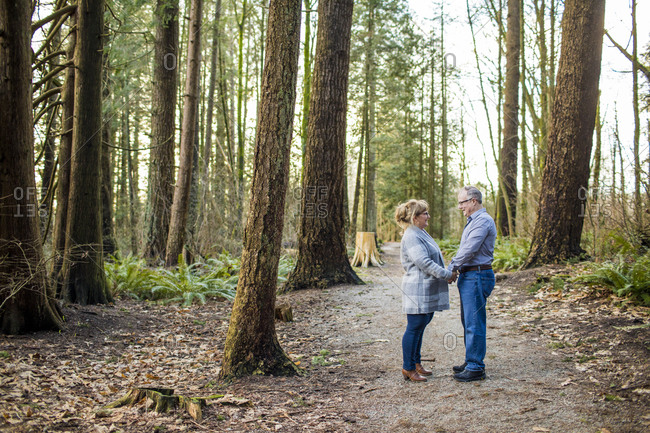 Older couple holding hands and looking at each other in the forest.