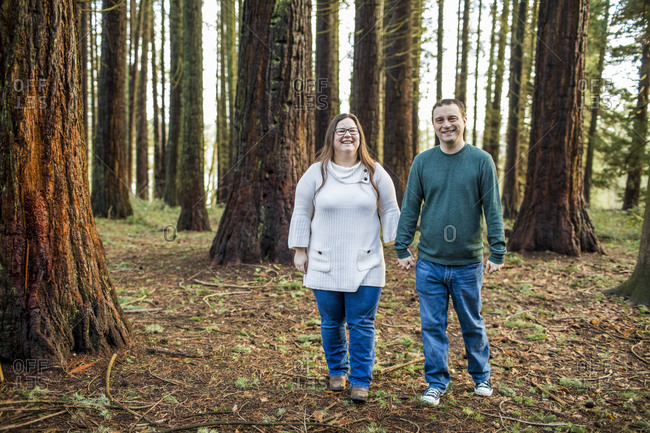 Happy couple enjoying walk through a forested park