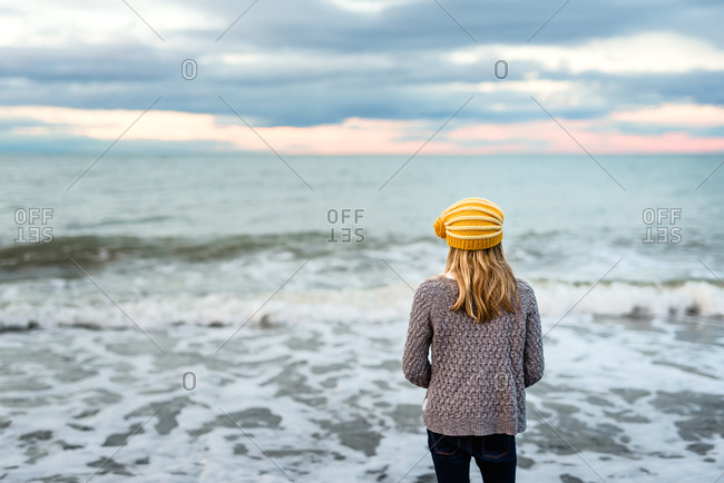 Tween girl wearing yellow knit hat looking at ocean at dusk