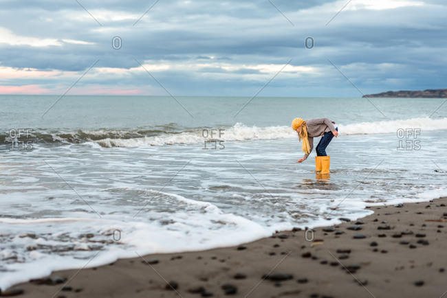 Preteen with yellow boots picking up shell from New Zealand beach