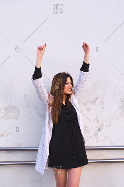 Natural young woman dressed in modern clothes makes funny gesture