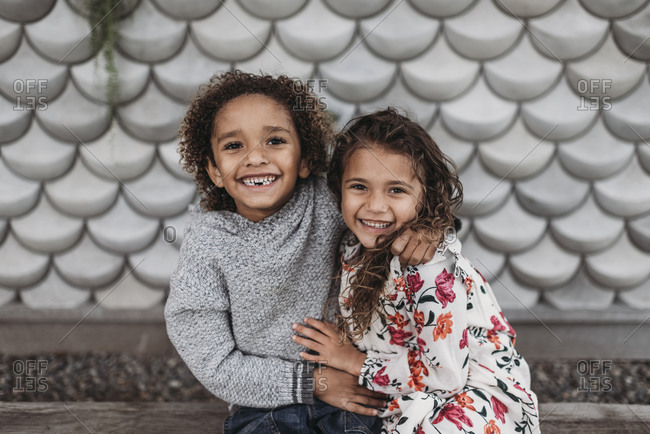 Cute siblings smiling and laughing while hugging