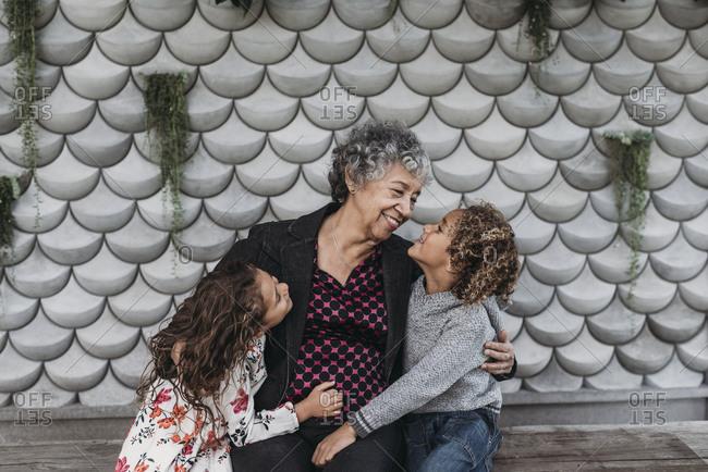 Portrait of sweet grandmother sitting close with twin grandchildren