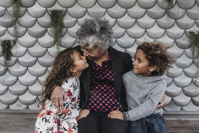 Portrait of grandmother sitting close with twin grandchildren