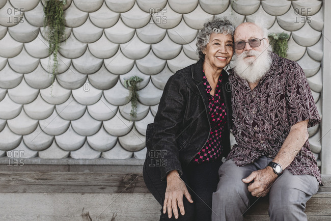Portrait of active senior couple sitting and smiling outside