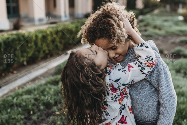 Twin brother kissing sisters cheek while standing outside at park