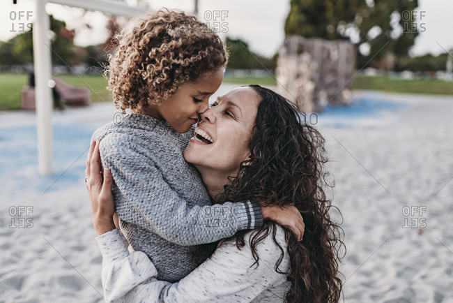 Close up of happy mother and son embracing closely on playground