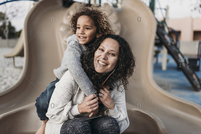 Son hugging happy mother on slide outside at park playground at dusk