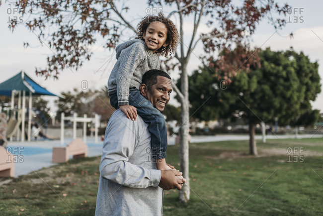 Cute boy sitting on happy father's shoulders at park playground