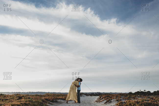 Wide view of mother and son on beach against cloudy blue sky