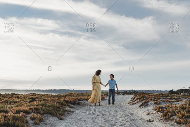 Wide angle of mother and son walking on beach against cloudy blue sky