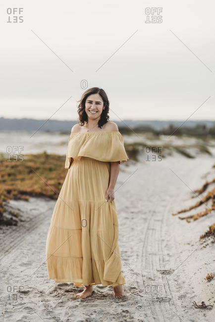Portrait of young woman standing on beach against cloudy sky smiling