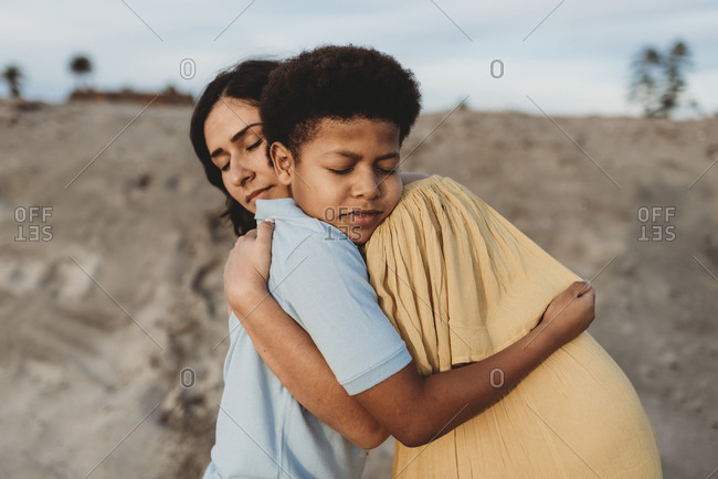 Close up of young mother and happy son embracing on beach