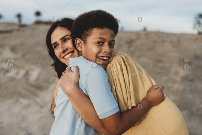 Close up of young mother and happy son embracing on beach at sunset