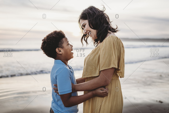 Side view of beautiful mother embracing son at seashore during sunset