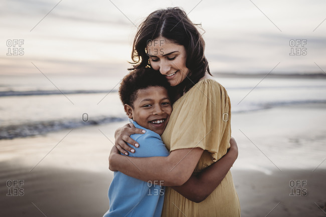 Portrait of beautiful mother embracing son at seashore during sunset