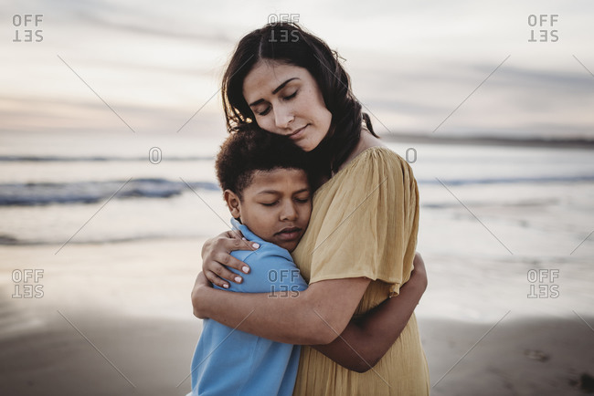 Portrait of mother embracing son during sunset with eyes closed