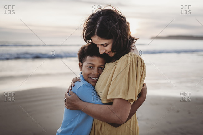 Portrait of beautiful mother hugging young son at beach during sunset