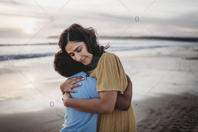 Side view of beautiful mother hugging son at seashore during sunset