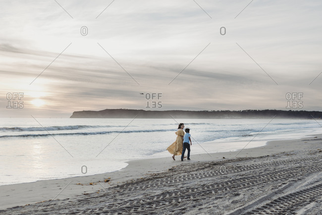 Young mother with dress and son walking on beach during cloudy sunset