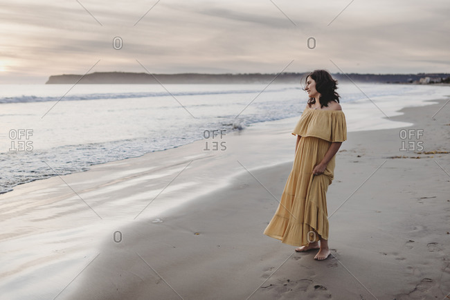 Lifestyle portrait of young woman standing on beach against cloudy sky