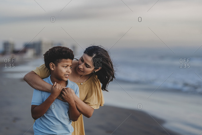 Close up of mother embracing school-aged boy at beach