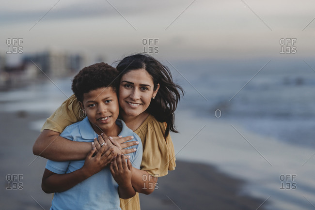 Close up portrait of mother hugging school-aged boy at beach smiling