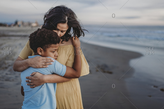 Young son and mother embracing at beach during sunset with cloudy sky