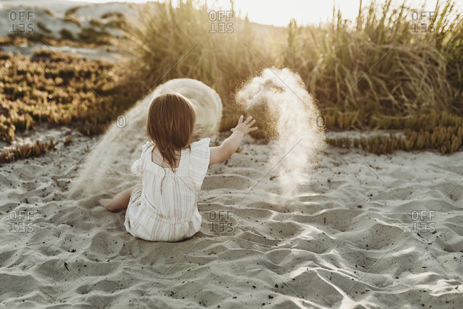 Behind view of young toddler girl throwing sand at sunset