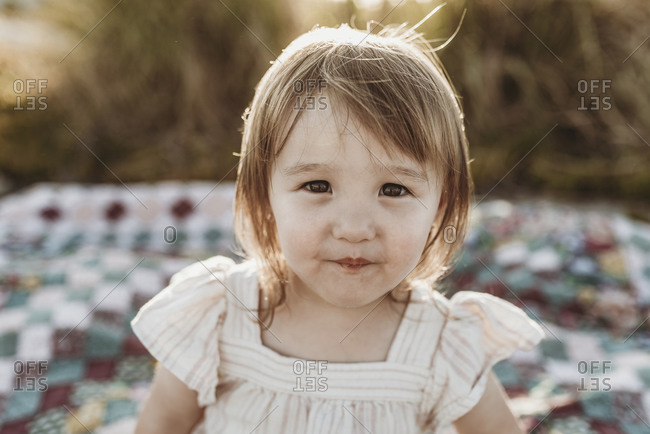 Close up portrait of young preschool-aged shy girl smiling