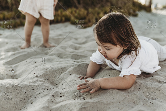 Close up of 2 year old playing in sand at beach while sister looks on