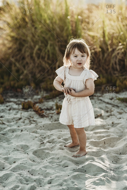 Full length of 2 year-old girl standing at beach during sunset