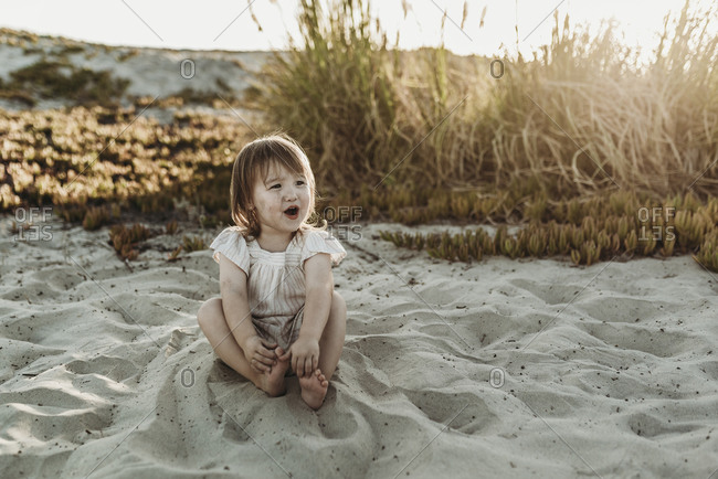 Front view of young toddler girl looking away and laughing at beach