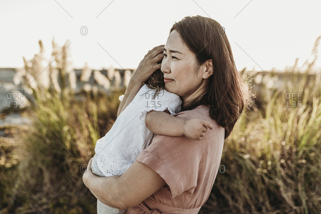 Mid view of happy mom embracing young toddler at beach during sunset