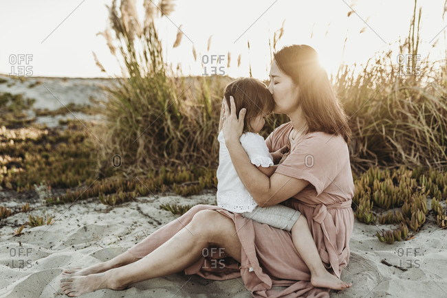 Side view of mother kissing young toddler at beach during sunset