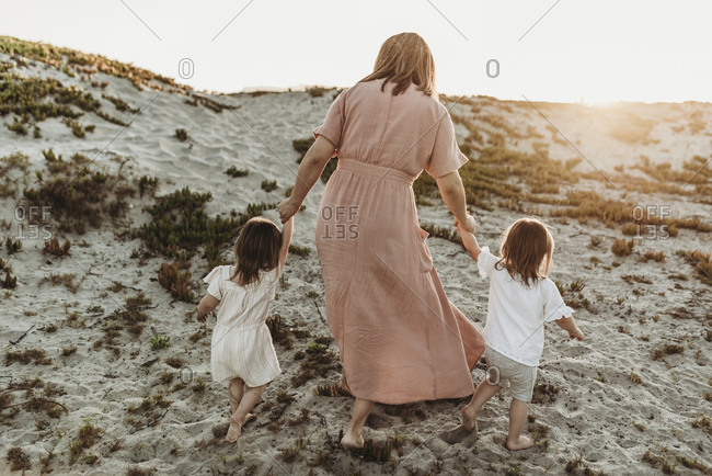 Behind view of mother walking toddler twins in sand to go to the ocean