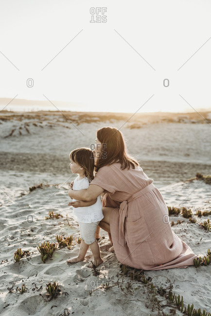 Side view of mother embracing toddler twins at beach