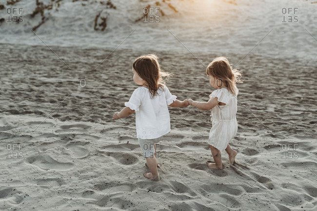 Side view of young toddler girls holding hands and walking at beach