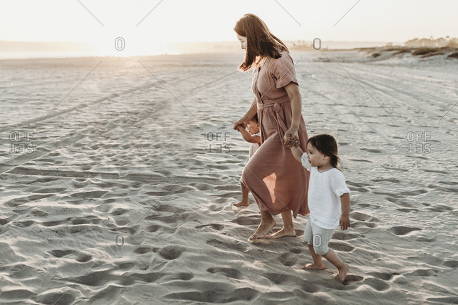 Side view of mother walking toddler twins to ocean with sun setting