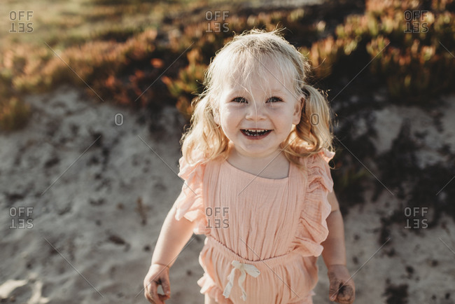 Portrait of young toddler girl with pigtails smiling on beach