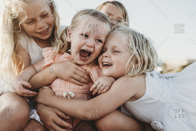 Close up of toddler laughing surrounded by young sisters