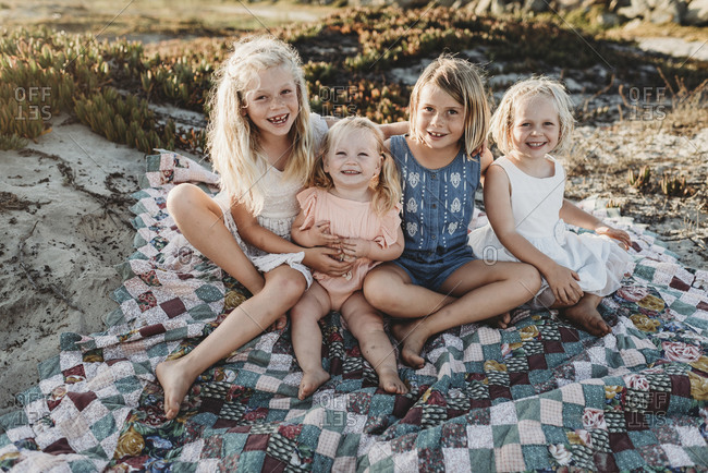 Four sisters sitting on blanket at beach smiling at sunset